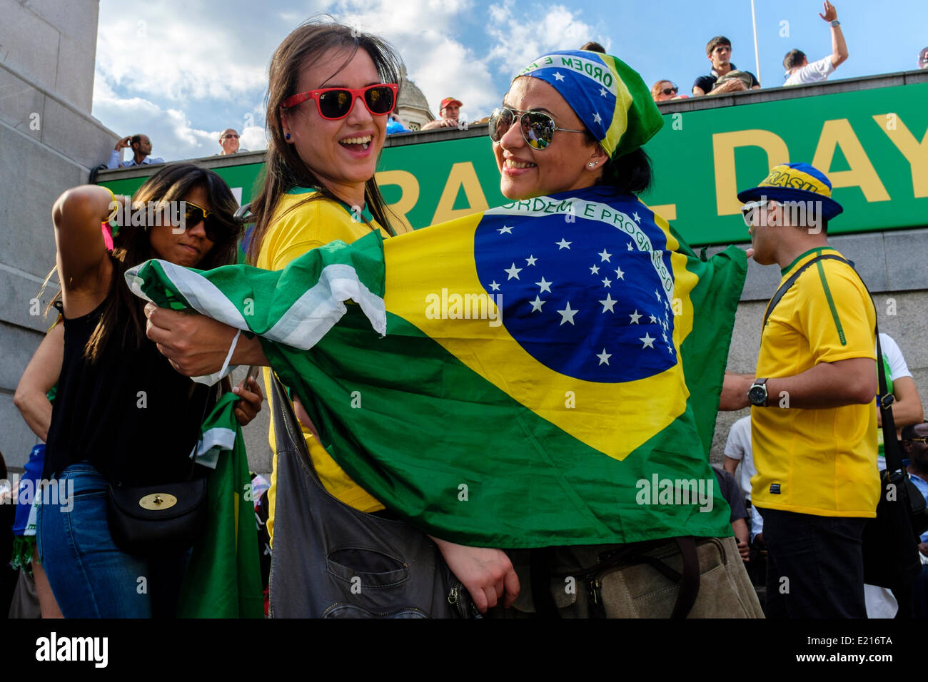 Two young women drape themselves in the Brazilian flag during Brazil Day celebrations in Trafalgar Square, London - Stock Image