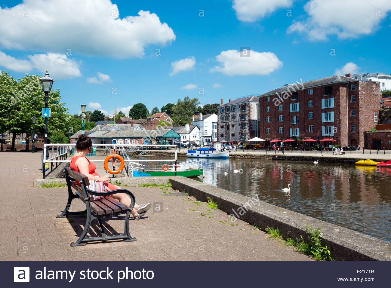 Young woman sitting on a bench at The Quay, Exeter, Devon, UK. - Stock Image