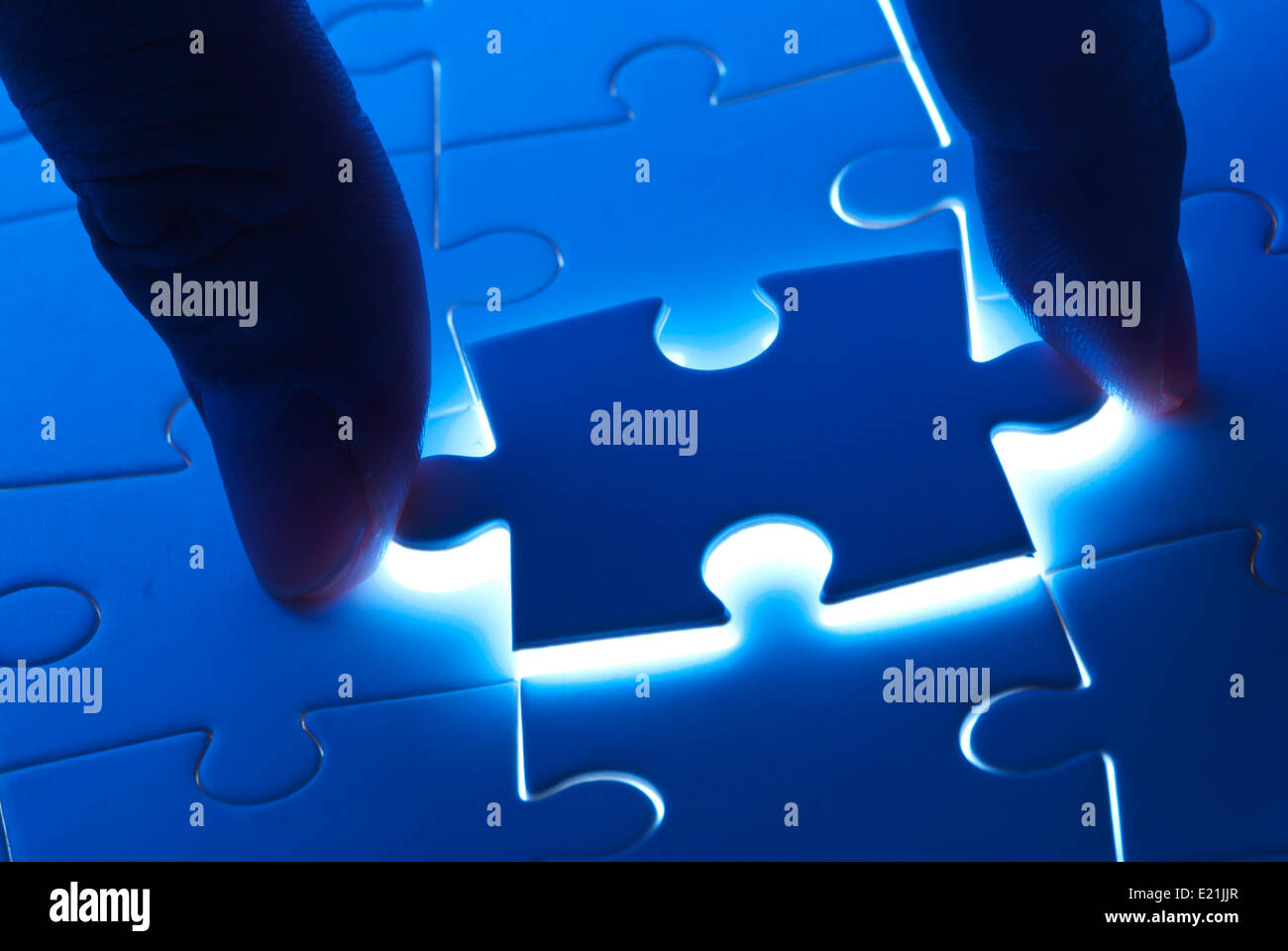 Pick puzzle piece with mystery light - Stock Image