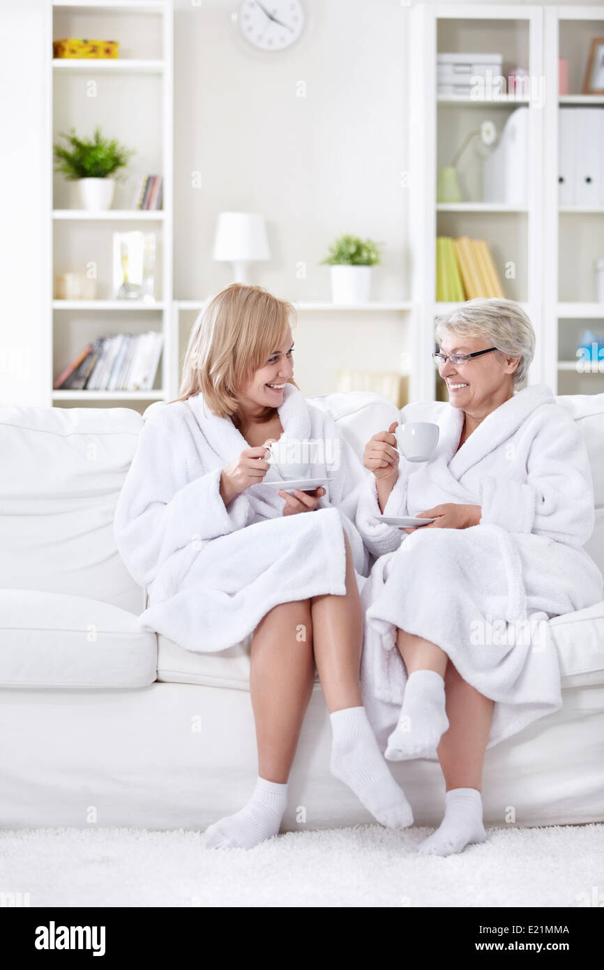 Mom with grown-up daughter tea on the couch - Stock Image