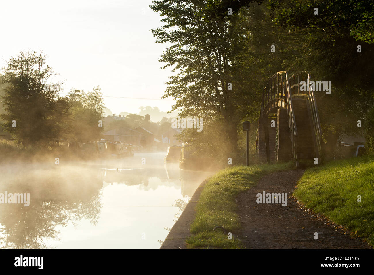 Canal and towpath foot bridge on the Grand Union Canal at Braunston in the early morning mist. Northamptonshire, - Stock Image