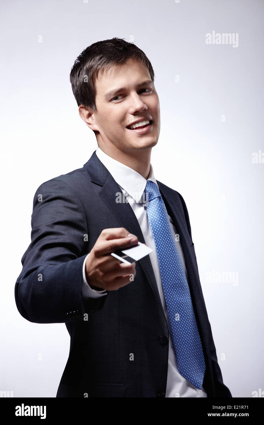 Businessman holds out a credit card - Stock Image