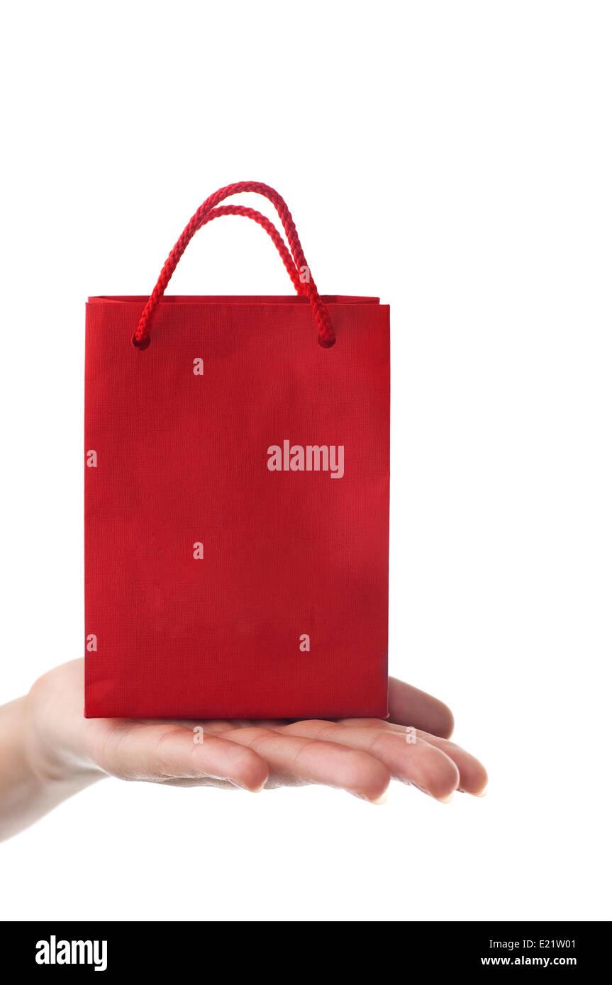 female hand holding red gift bag - Stock Image
