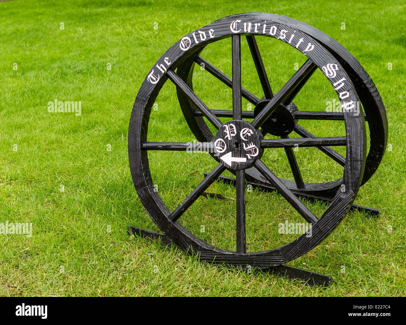 Two old cart wheels have been creatively used to form a shop sign - Stock Image