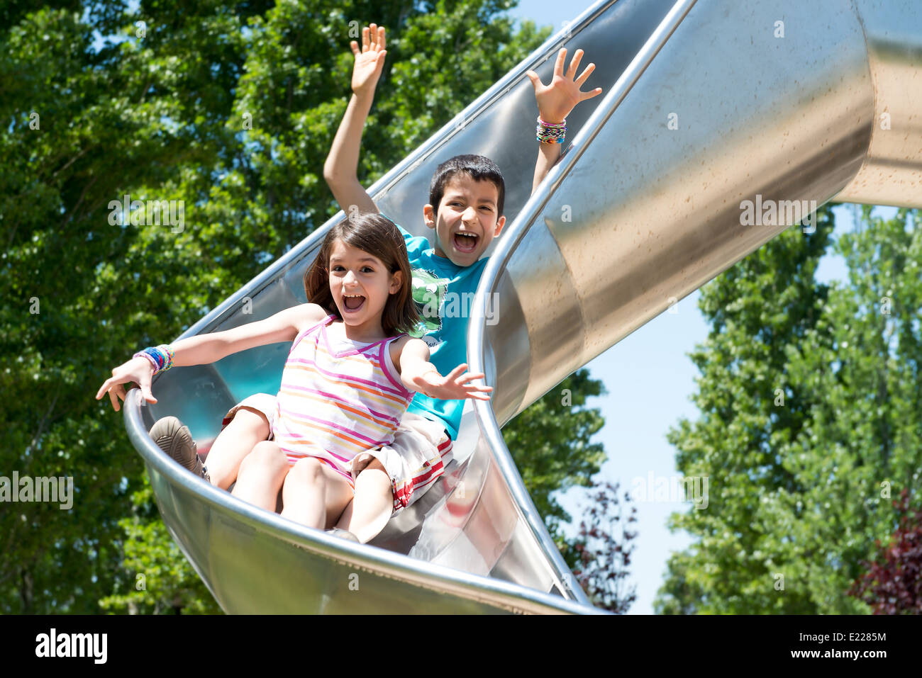 Young kids riding the slider in the park - Stock Image