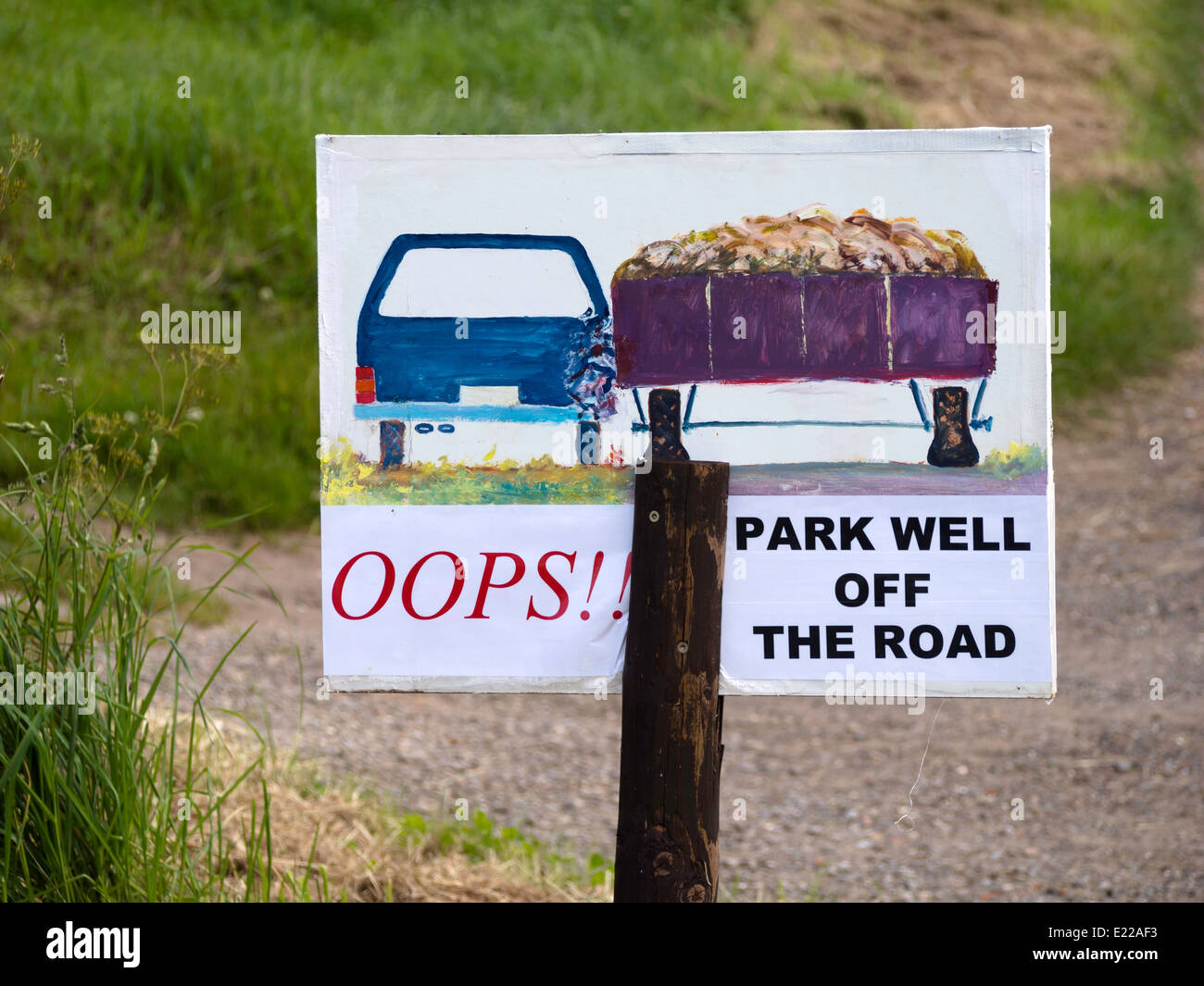 Warning sign advising drivers to park well off the road to avoid damage by passing wide agricultural vehicles - Stock Image