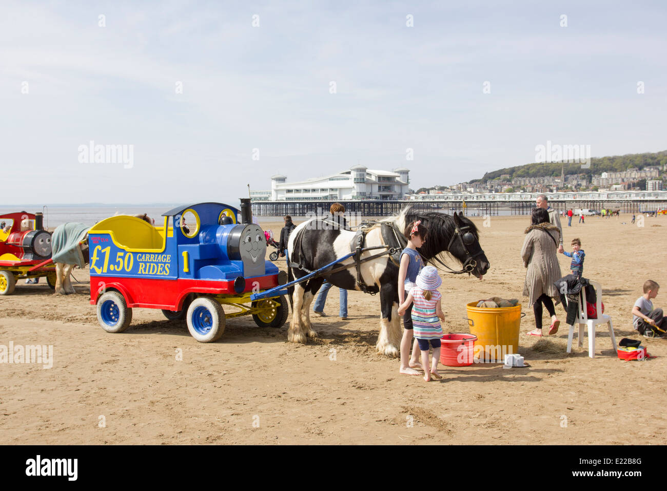 Horses pulling Thomas the Tank Engine carts on the beach in