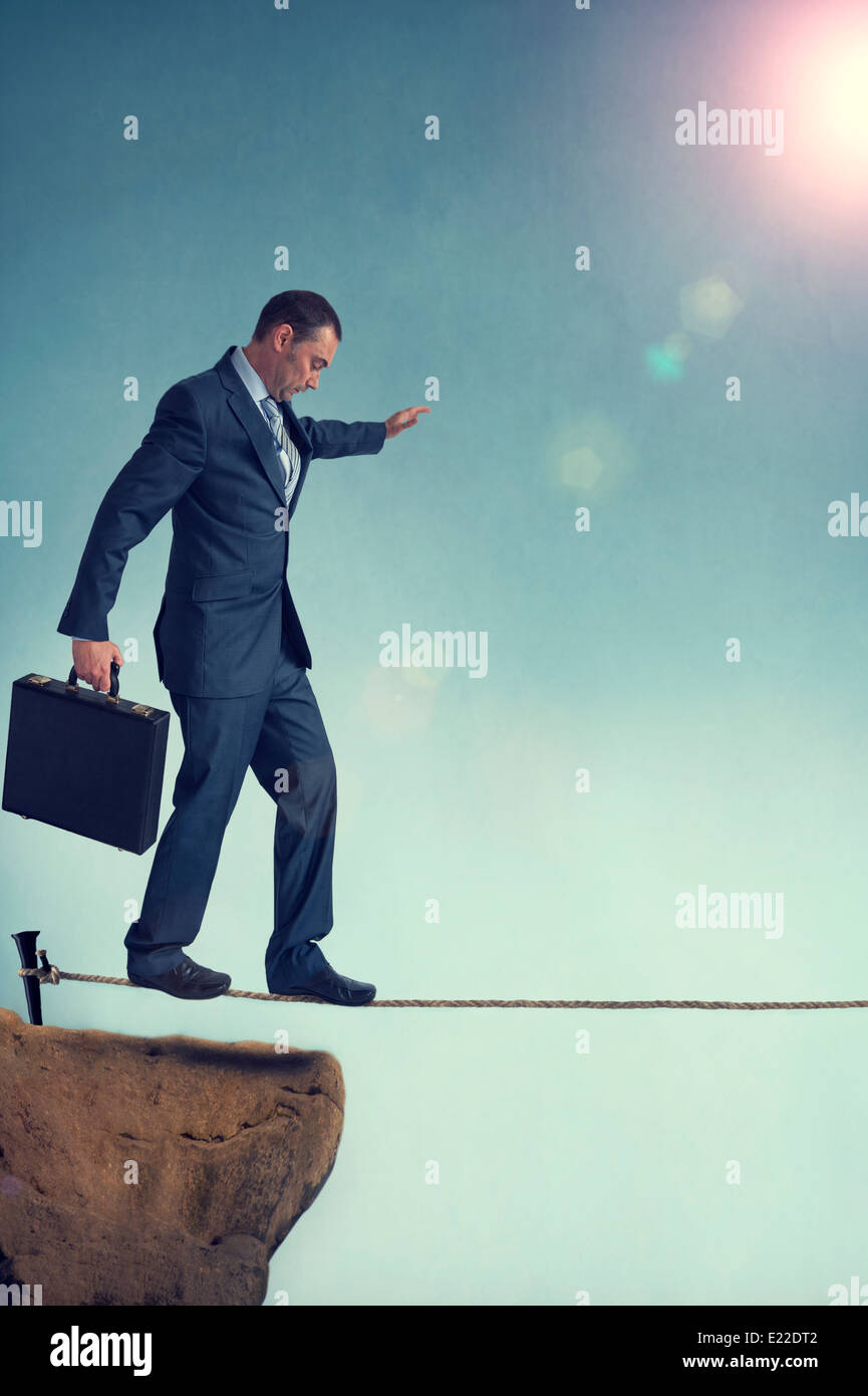 balancing businessman starting out on a tightrope - Stock Image