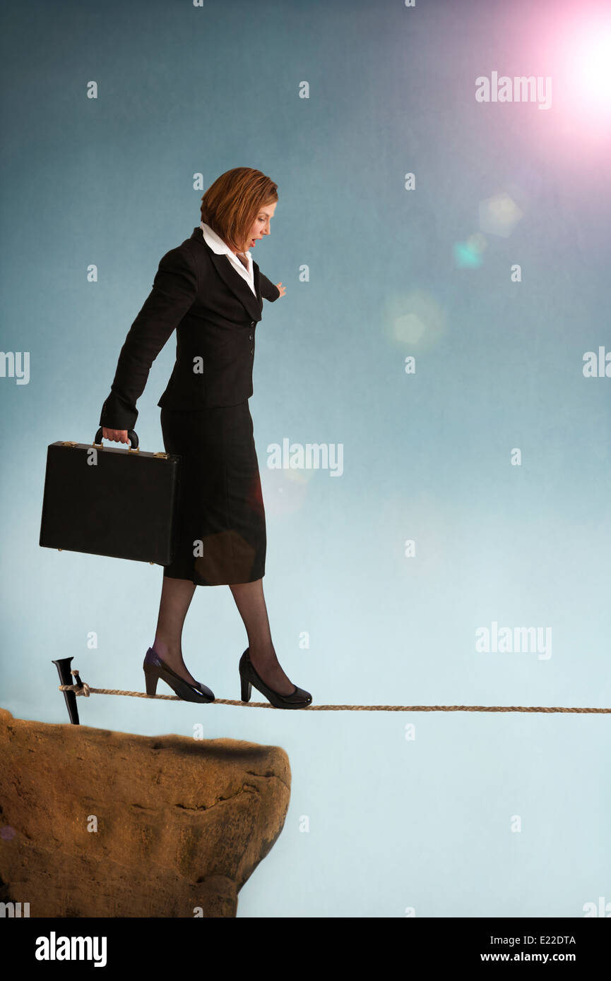 businesswoman starting out on a tightrope or highwire illustrating the concept of business risk - Stock Image