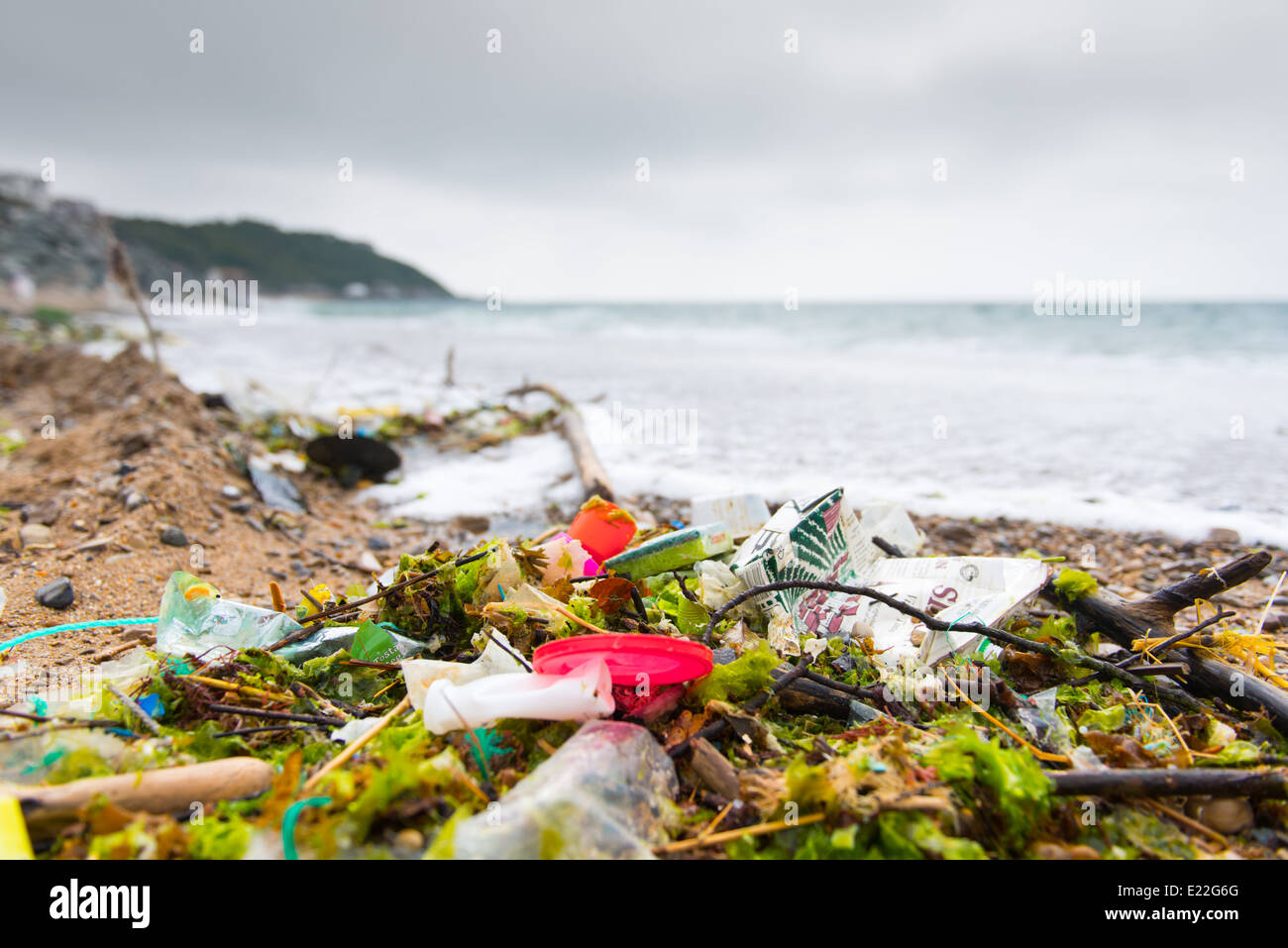 Plastic bags, bottles, and containers washed up on the beach. - Stock Image