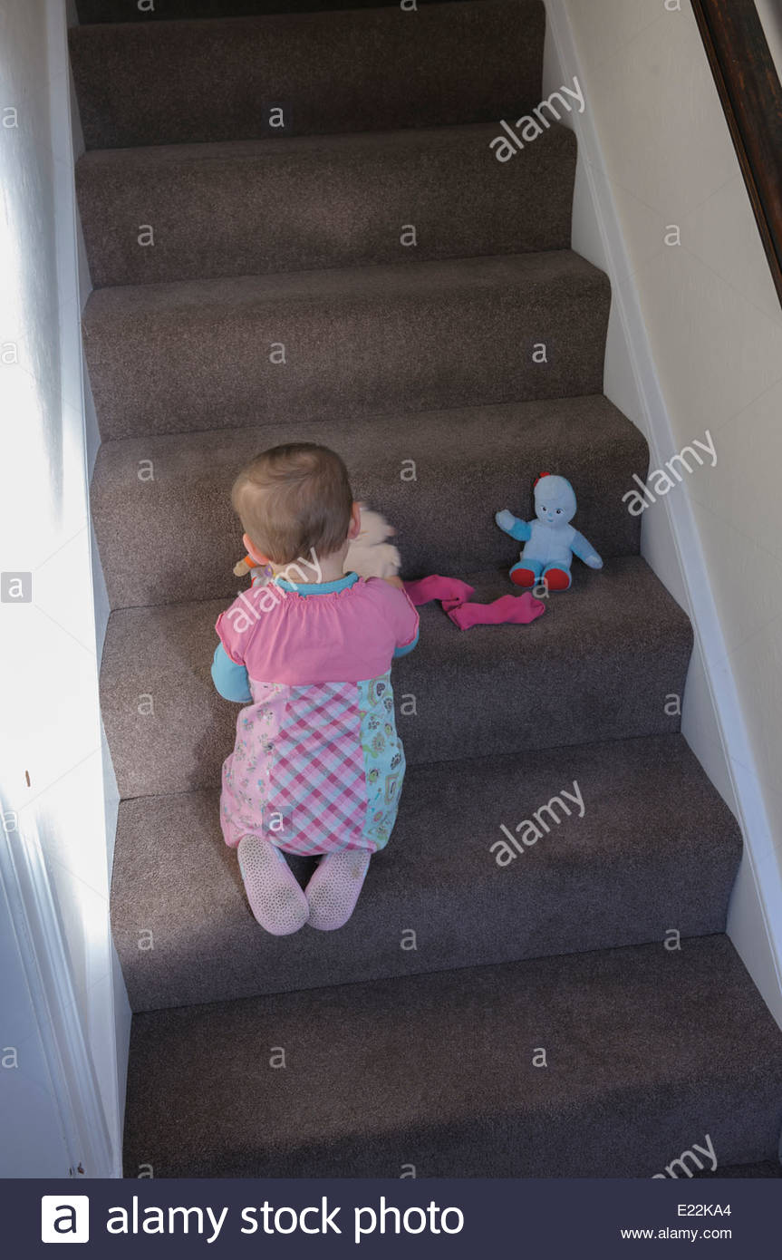 A small child playing alone on a flight of stairs - Stock Image