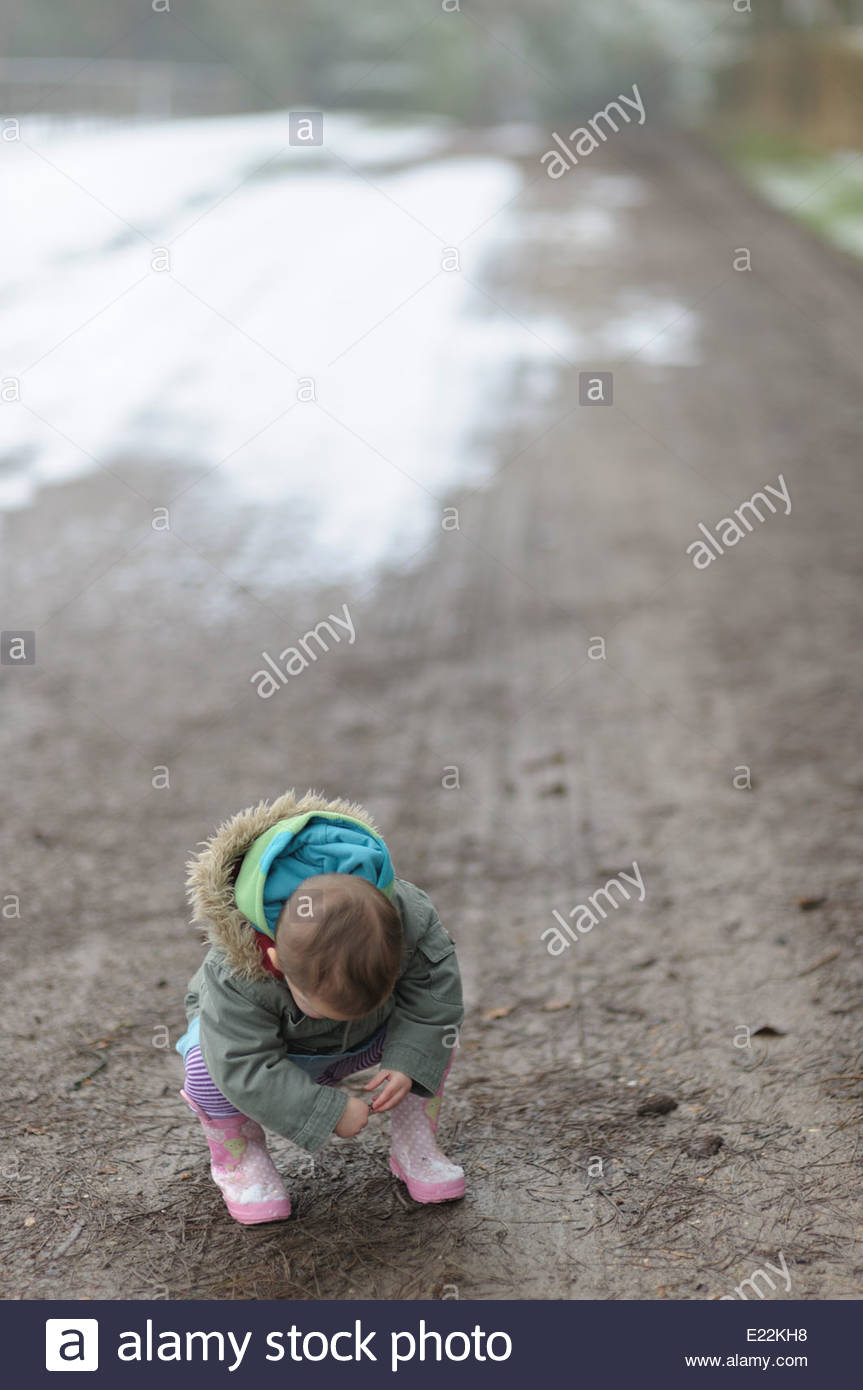 A small child alone on a road, looking down at the surface. - Stock Image