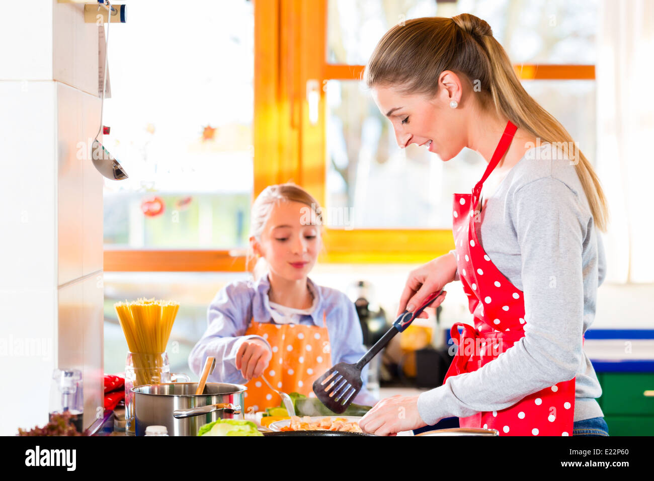 Mother showing daughter how to cook in domestic kitchen - Stock Image