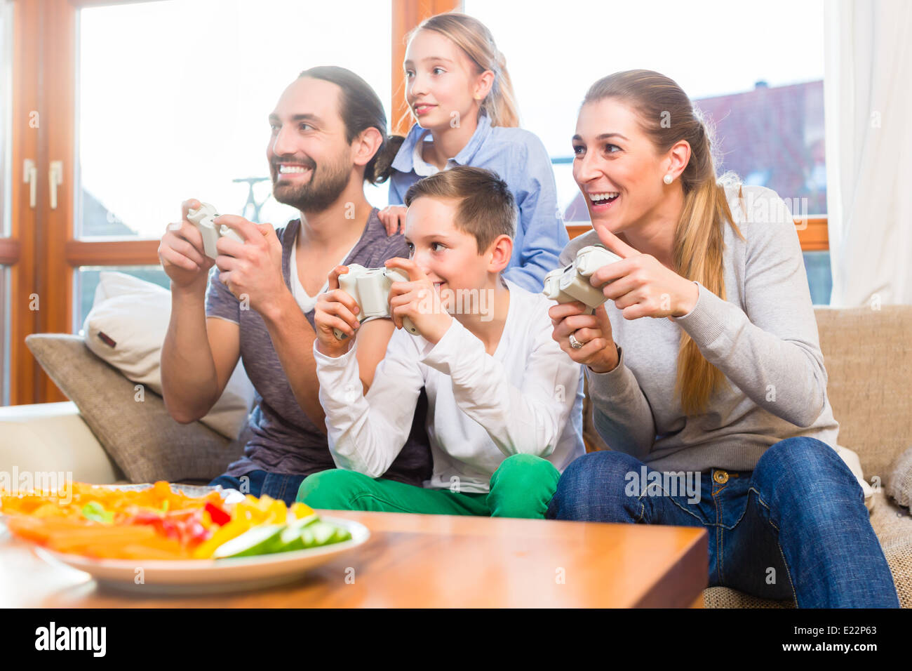Family having leisure time together and playing with video game console - Stock Image