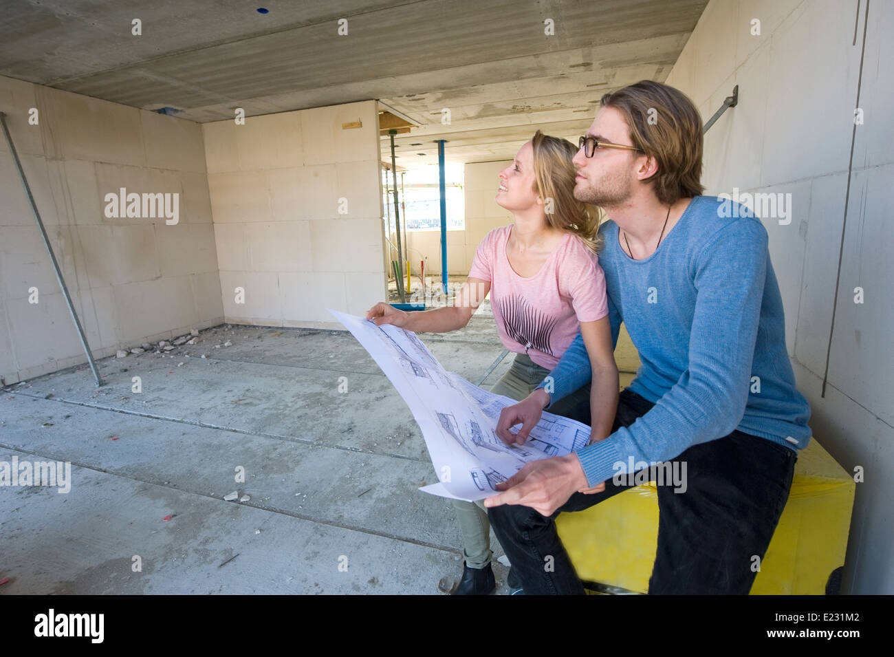 Building owners stock photos building owners stock images alamy young couple with blueprint is looking in the living room how their new home is being malvernweather Image collections