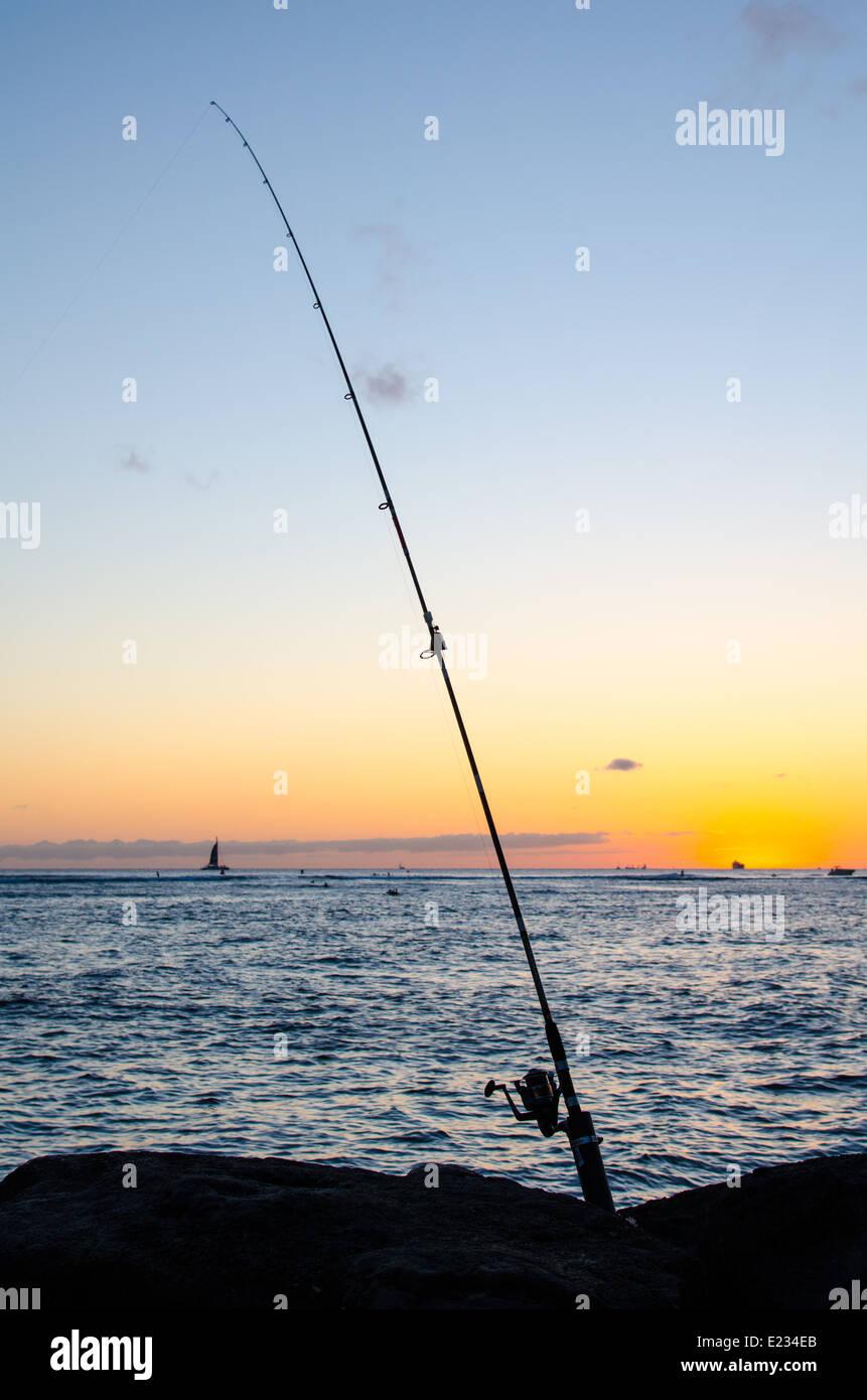 Silhouette of a fishing rod in the rocks on the breakwater in Waikiki, Oahu, Hawaii - Stock Image