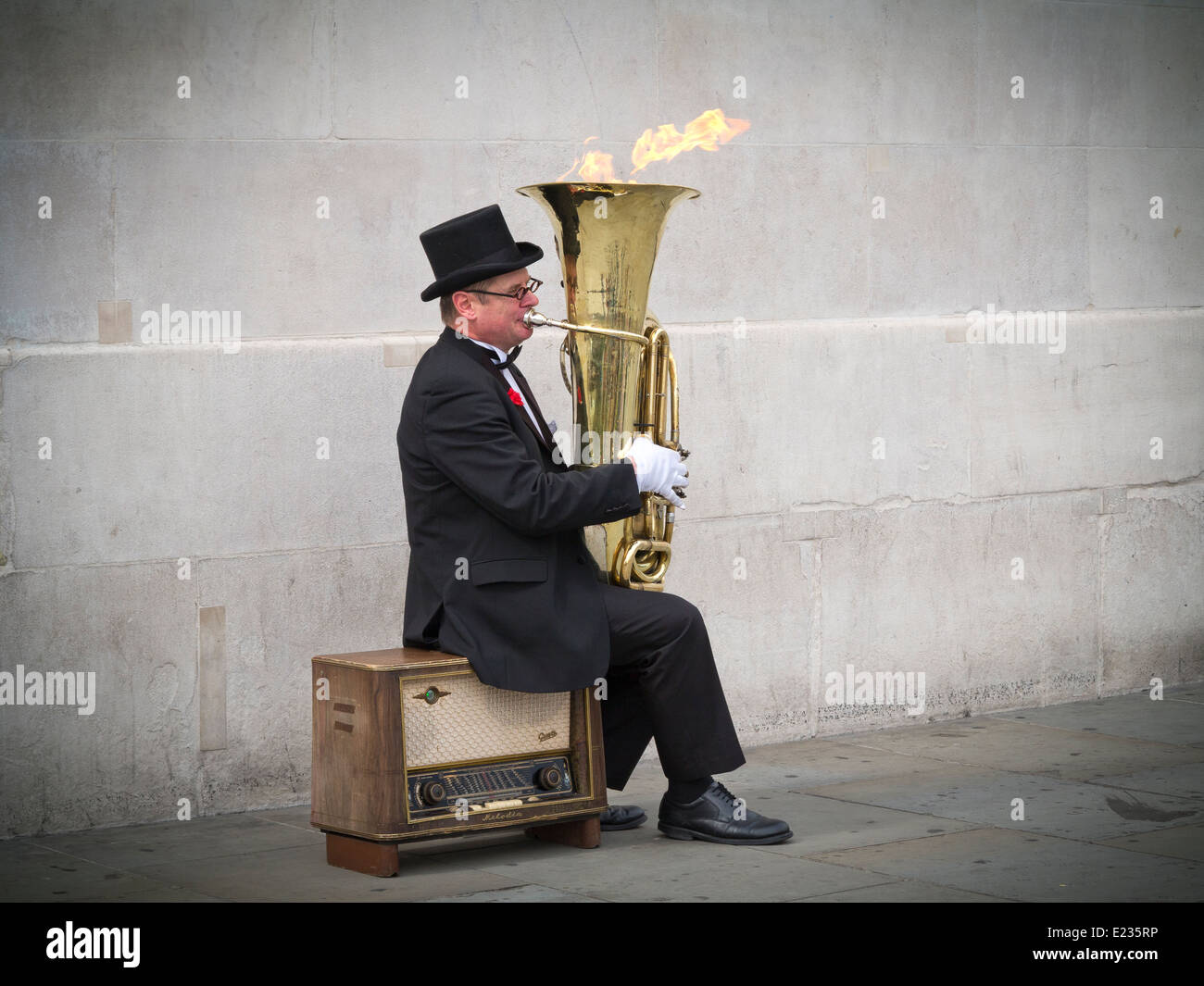 Busker, Christopher Werkowicz playing his flaming tuba sitting on an old radio against a plain stone wall London - Stock Image