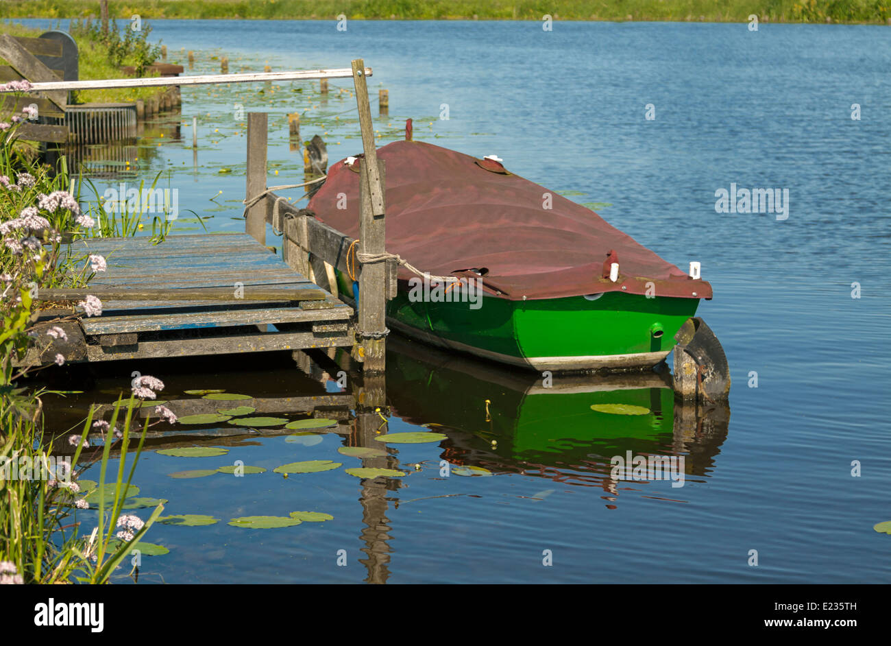Reflections of a moored flat-bottomed dingy on Kromme Does River, Hoogmade, Kaag and Braassem, South Holland, The - Stock Image