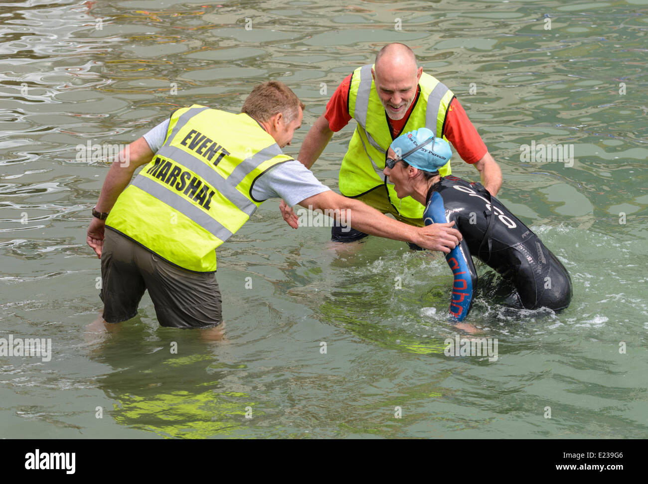 Swimmer being helped out of the river after finishing a swimming race. - Stock Image