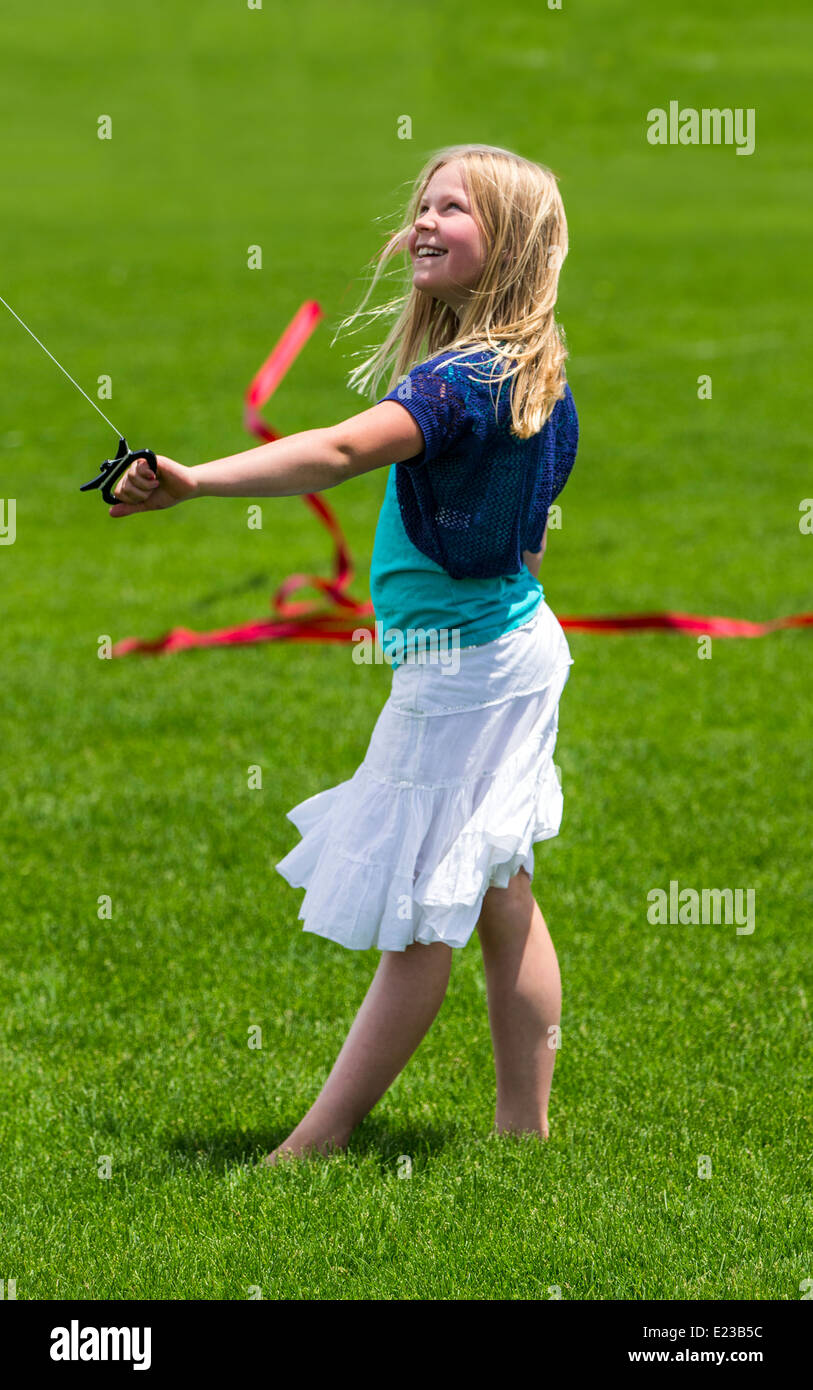 Young girl flying a kite on a grassy field - Stock Image