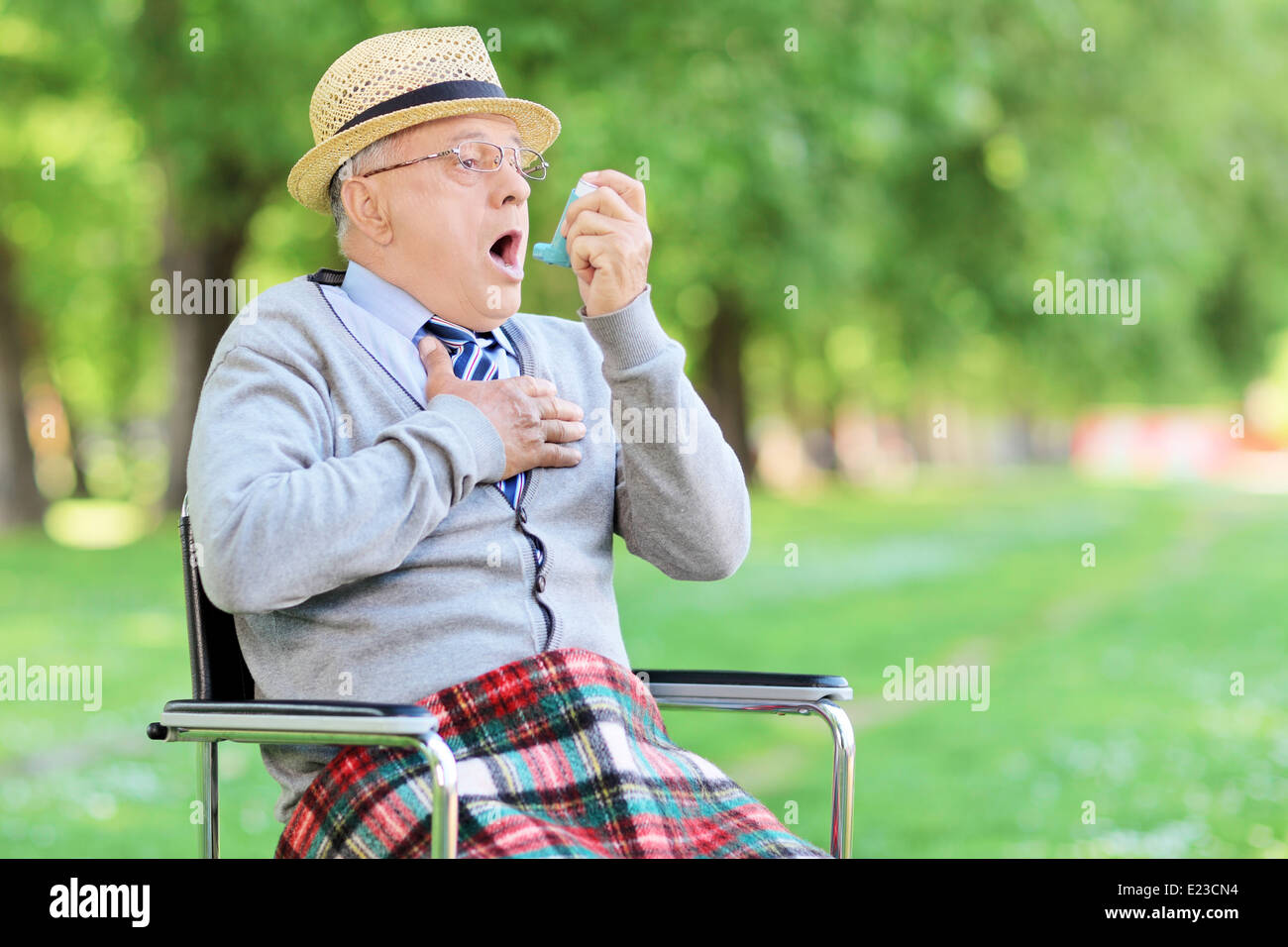 Senior man having an asthma attack in a park - Stock Image