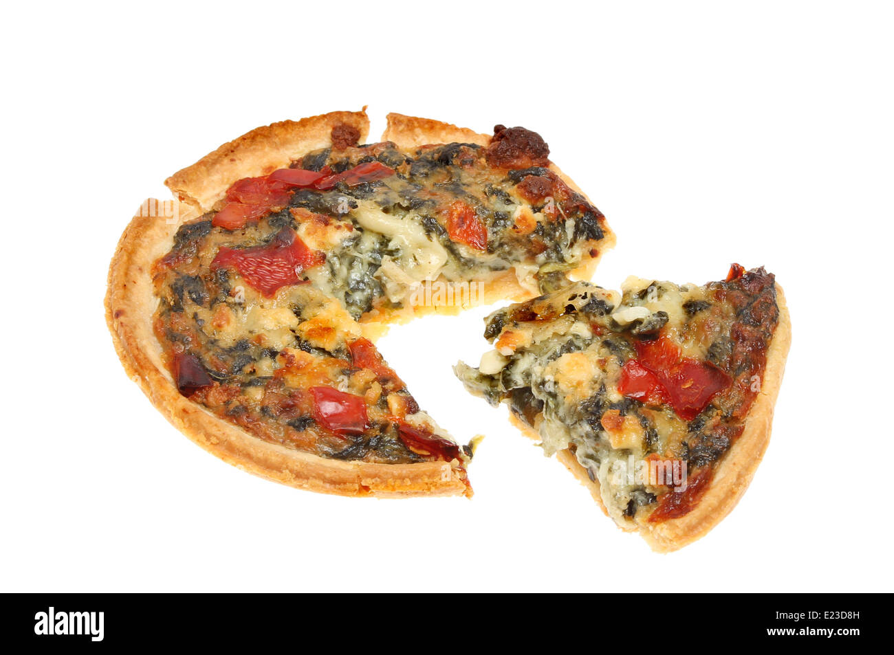 Spinach, feta cheese and tomato savory tart with a slice cut out isolated against white - Stock Image