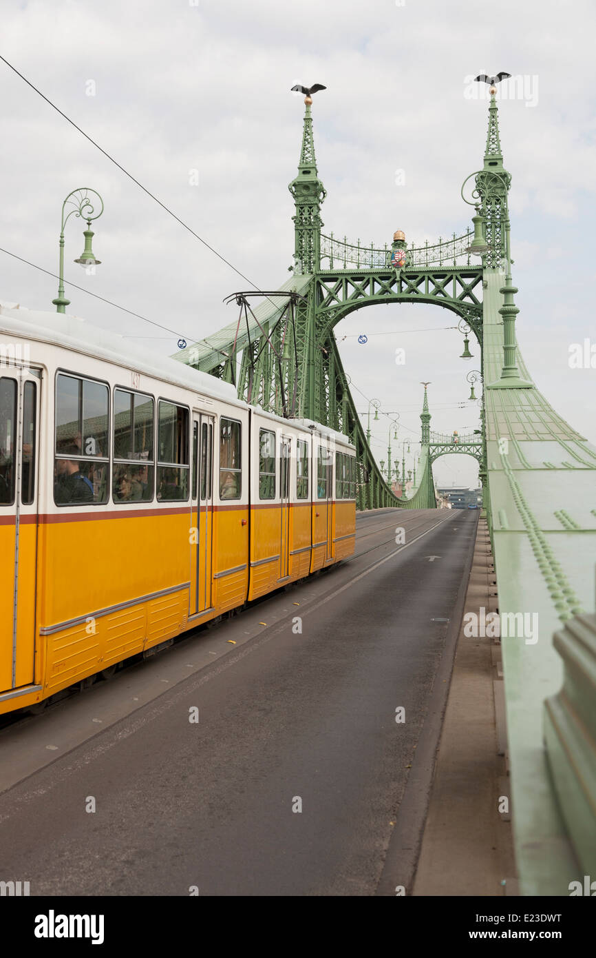 Yellow tram crossing the Liberty Bridge in Budapest, Hungary Stock Photo