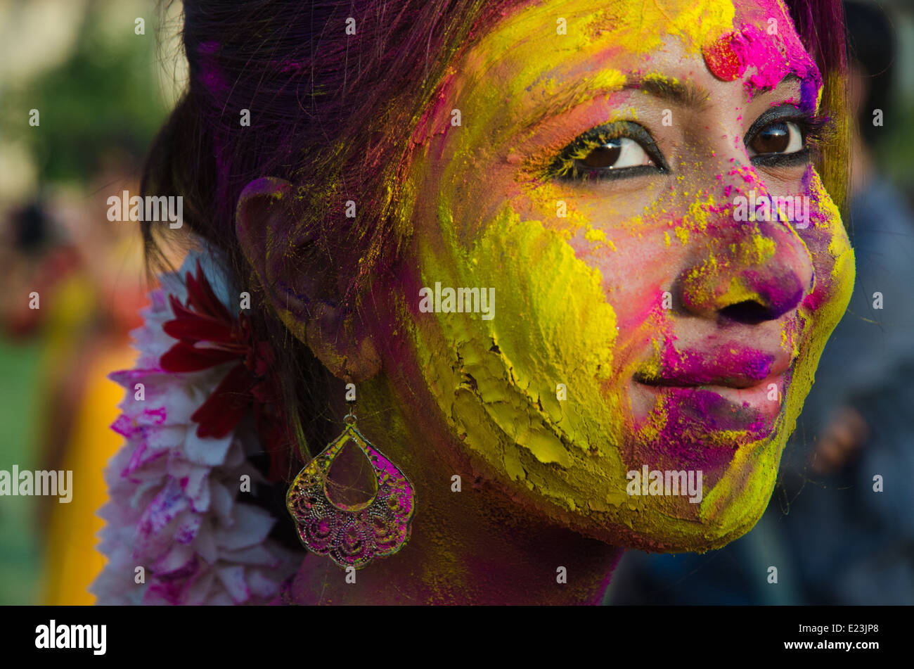 Portrait of an Indian woman with colors in her face at Holi festival. - Stock Image