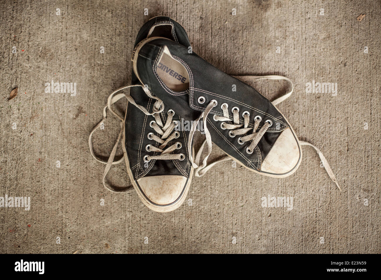 An old pair of trainers on a concrete background - Stock Image