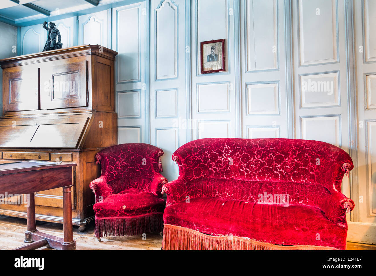 historic french living room with red chair and couch, on the wall a portrait photograph of general de gaulle, écomusée - Stock Image