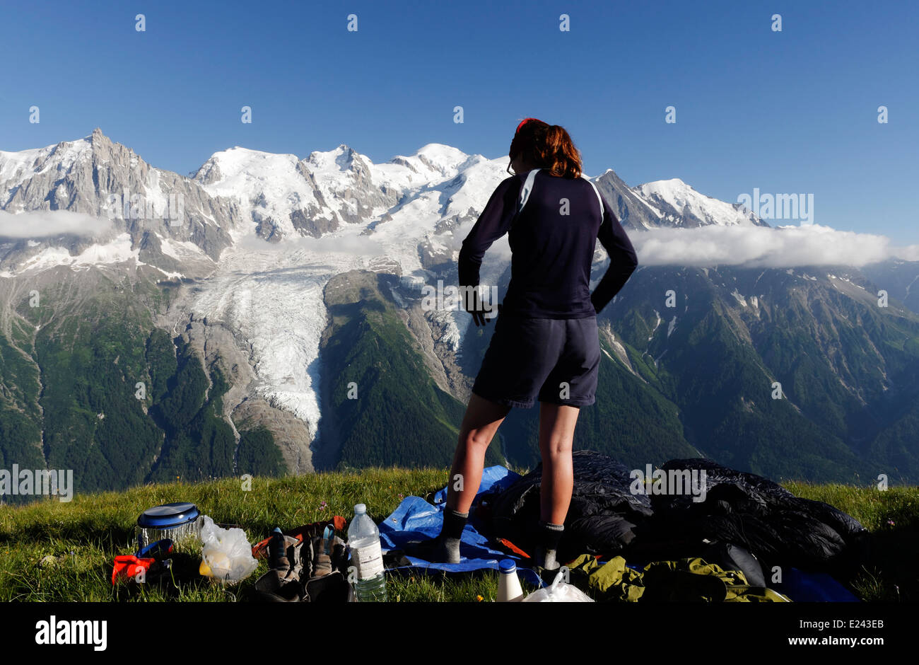 A lady at a wild camp on le Brevent  in the French Alps with the Mont Blanc massif beyond - Stock Image