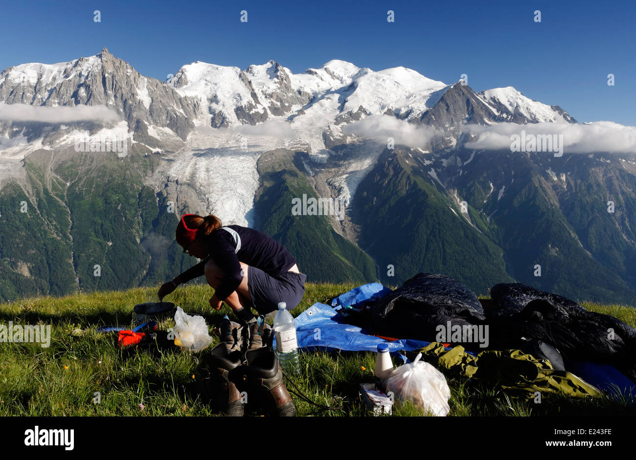A lady camper preparing food wild camping on le Brevent  in the French Alps with the Mont Blanc massif beyond - Stock Image
