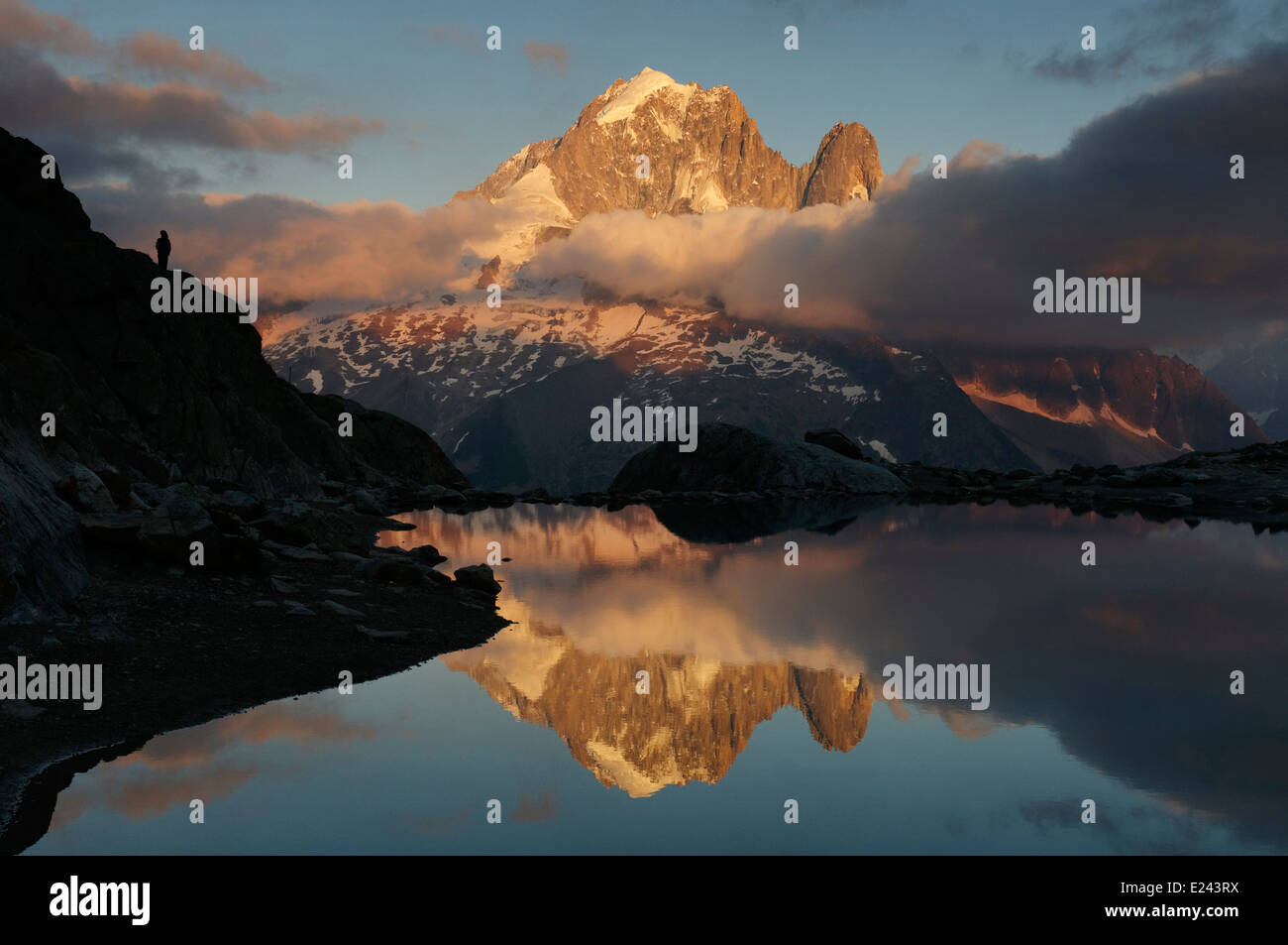 A lone person watcing sunset on the Aiguille Verte reflected in Lac Blanc, Chamonix, France Stock Photo