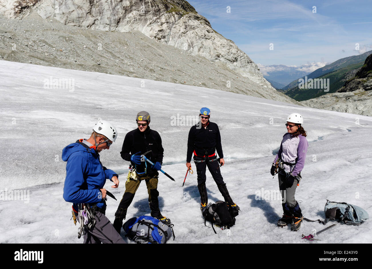 A guide demonstrating correct harness adjustment to three clients on an alpine climbing school - Stock Image