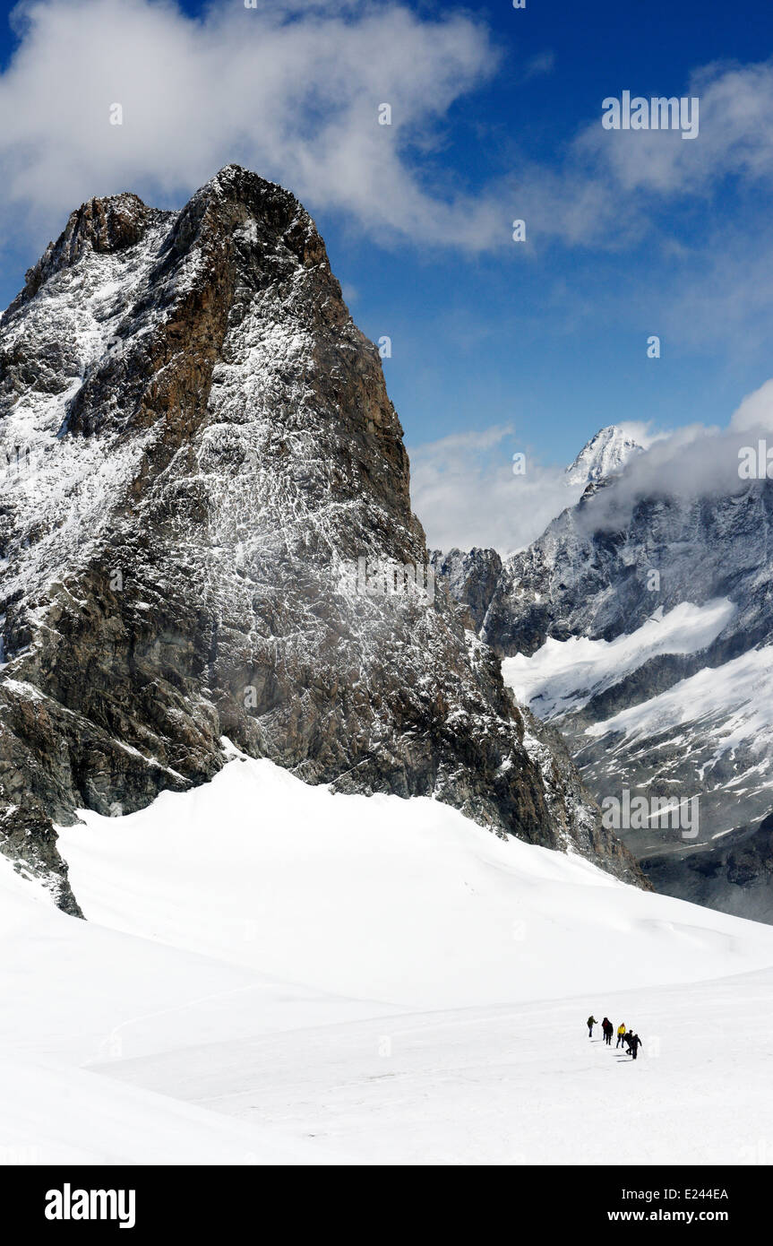 Figures of a mountaineering group high on Pigne d'Arolla near the Vignettes hut in the Swiss Alps, with L'Eveque Stock Photo