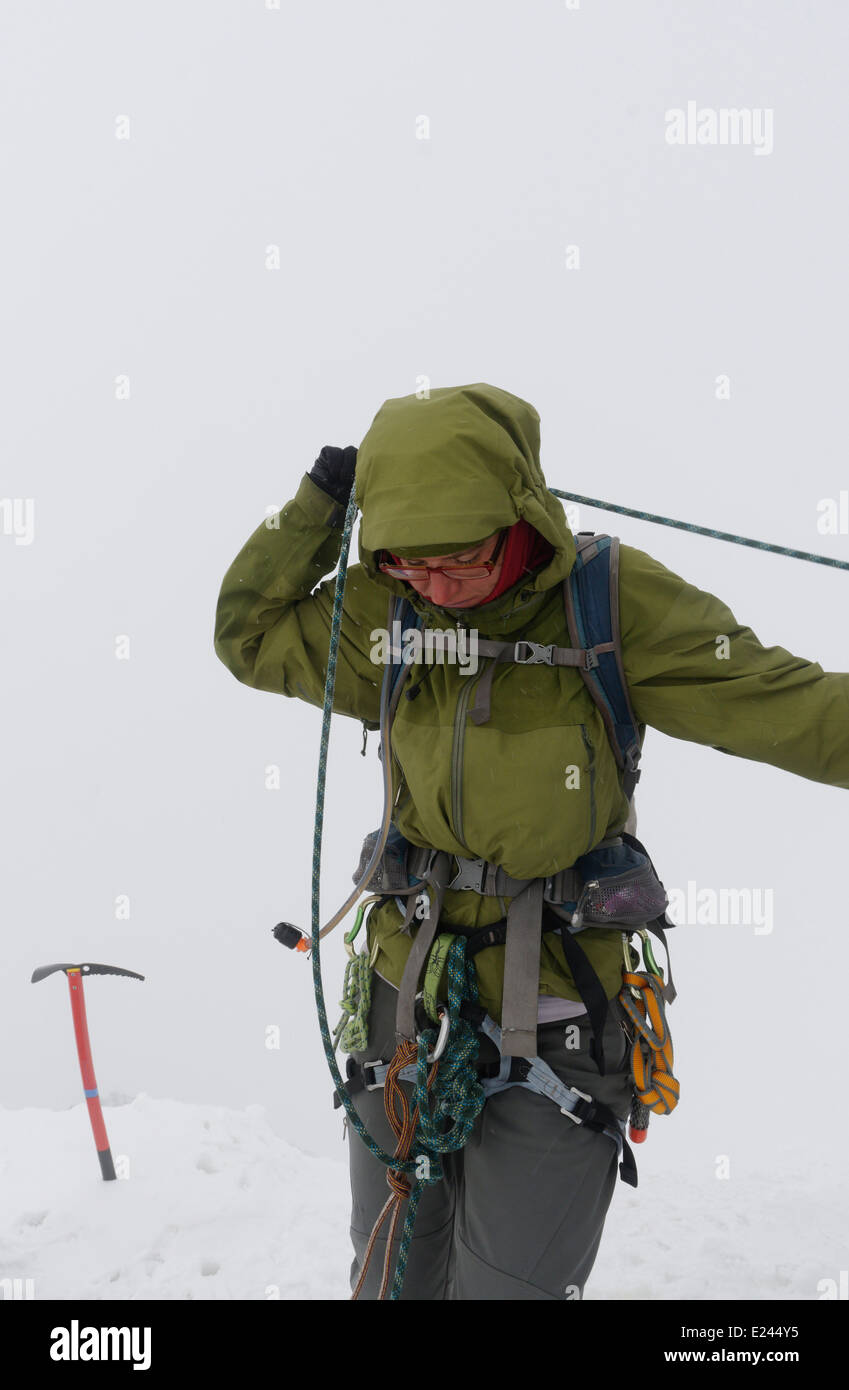 A lady mountaineer coiling rope around her neck on the summit of the Wildstrubel in the Swiss Alps - Stock Image