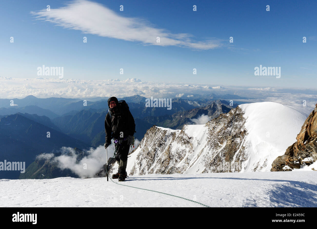 A climber pauses for a breather on the ascent of Monte Rosa in he Swiss Alps - Stock Image
