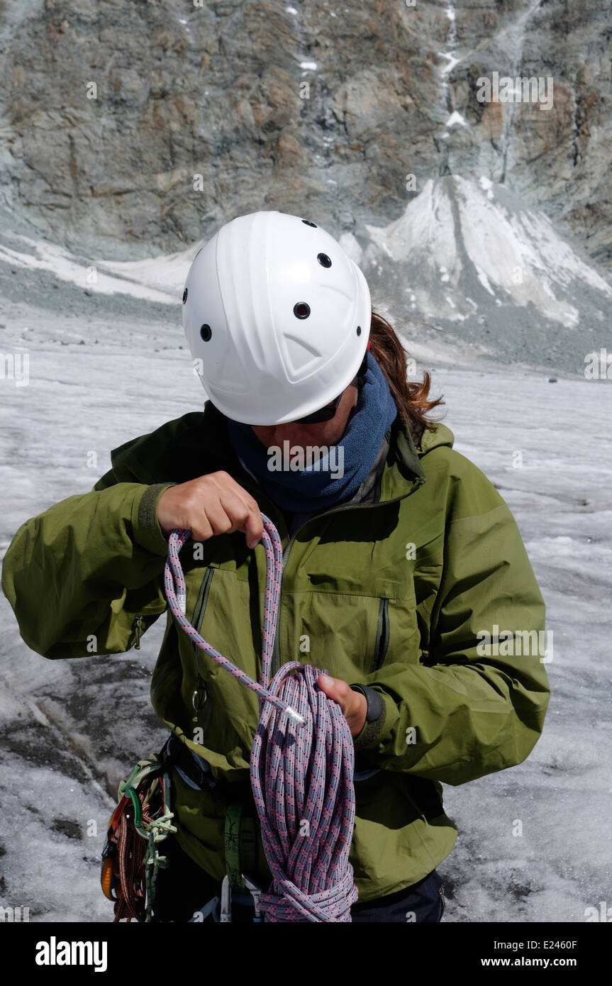 A lady mountaineer coiling a rope after a climb - Stock Image