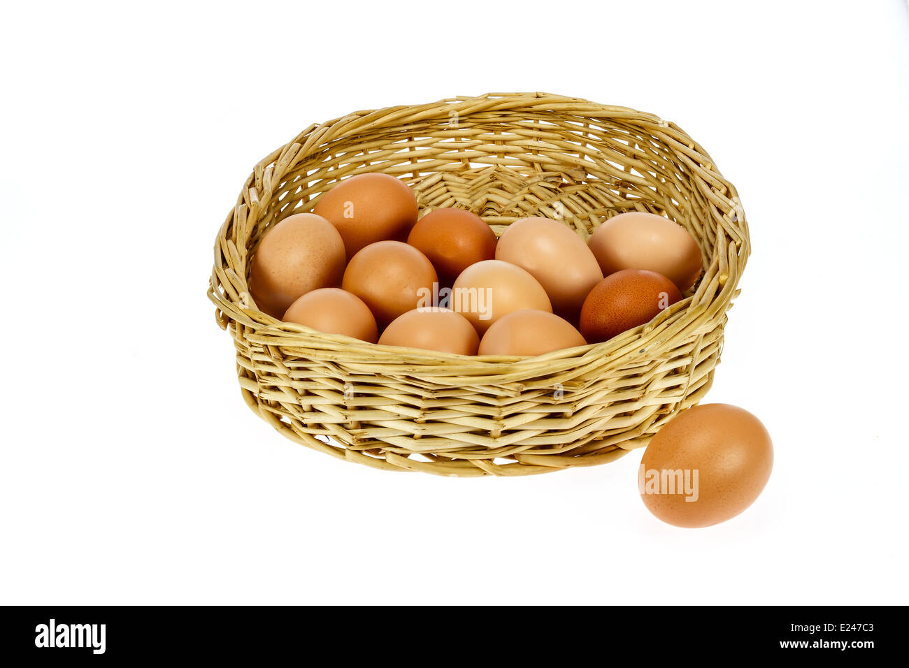 Brown eggs in a basket shot against a white background. - Stock Image