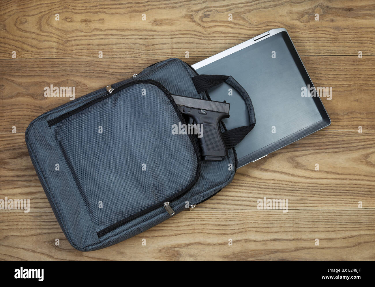 Overhead tilted view of laptop computer, personal weapon and carry case, on rustic wooden boards - Stock Image