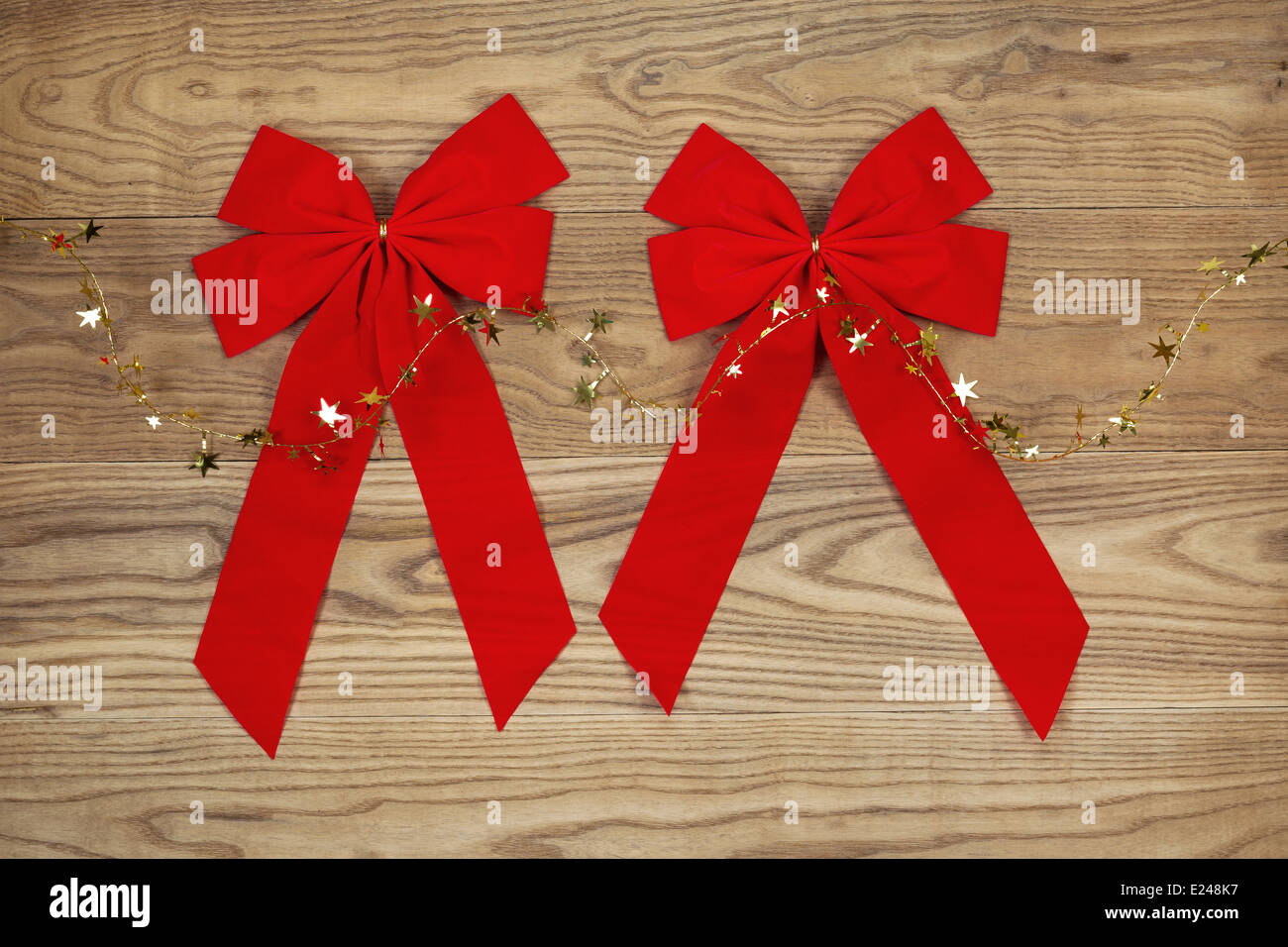 Overhead view of Christmas red bows and golden stars on string positioned on rustic wooden boards. - Stock Image