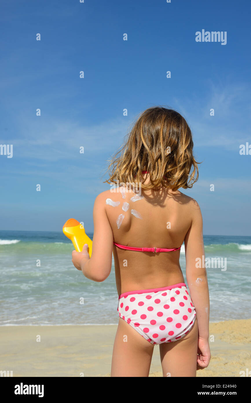 Child applying sunscreen on the beach during summer vacation - Stock Image
