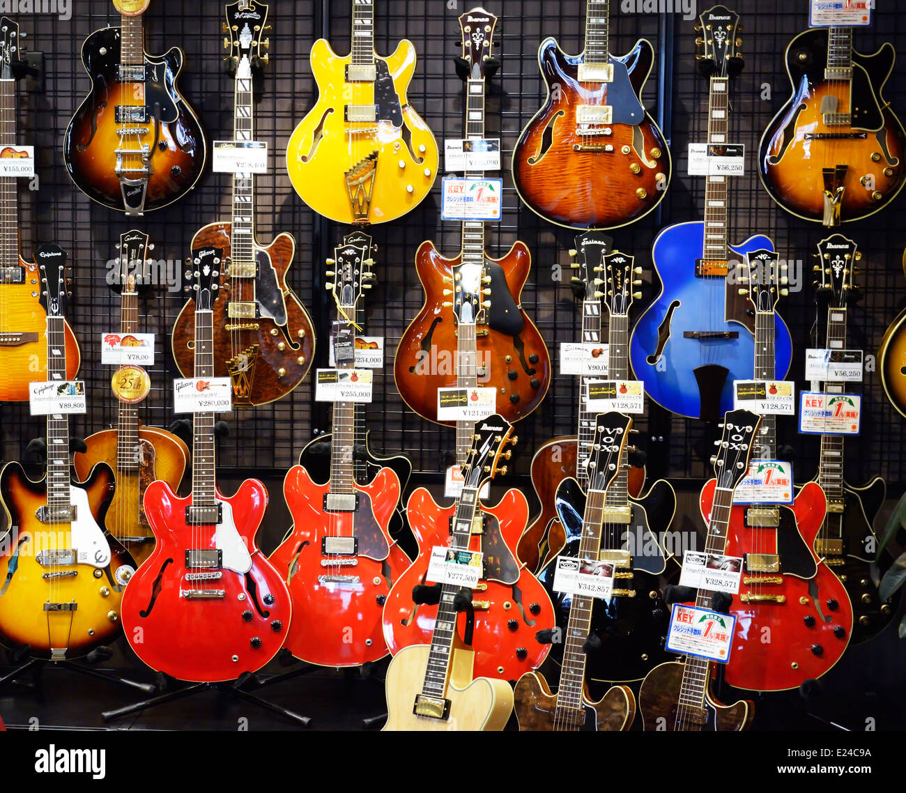 Semi-acoustic hollow-body electric guitars on display in a music store in Tokyo, Japan. - Stock Image