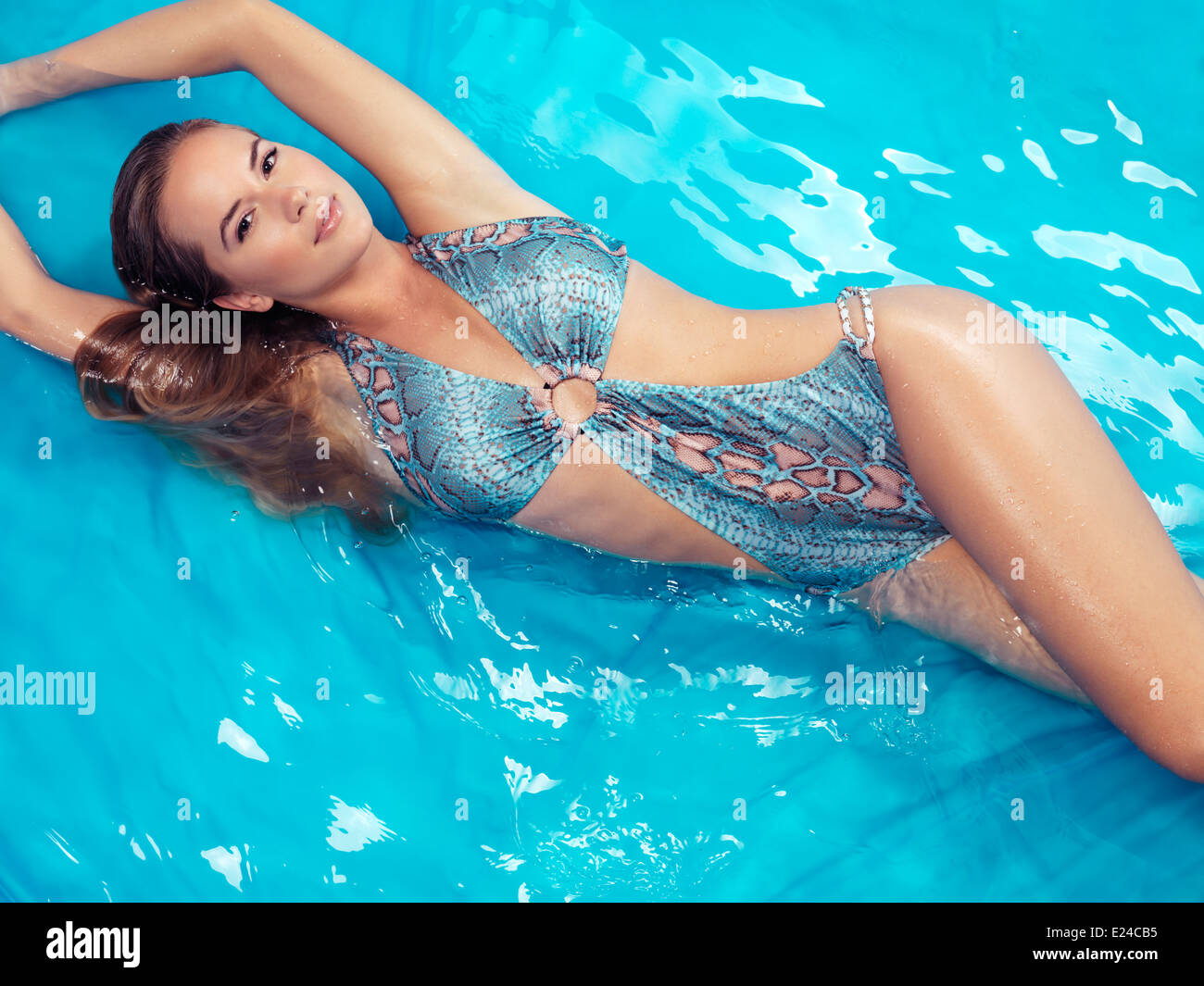 Young smiling woman wearing a swimsuit lying in blue water - Stock Image