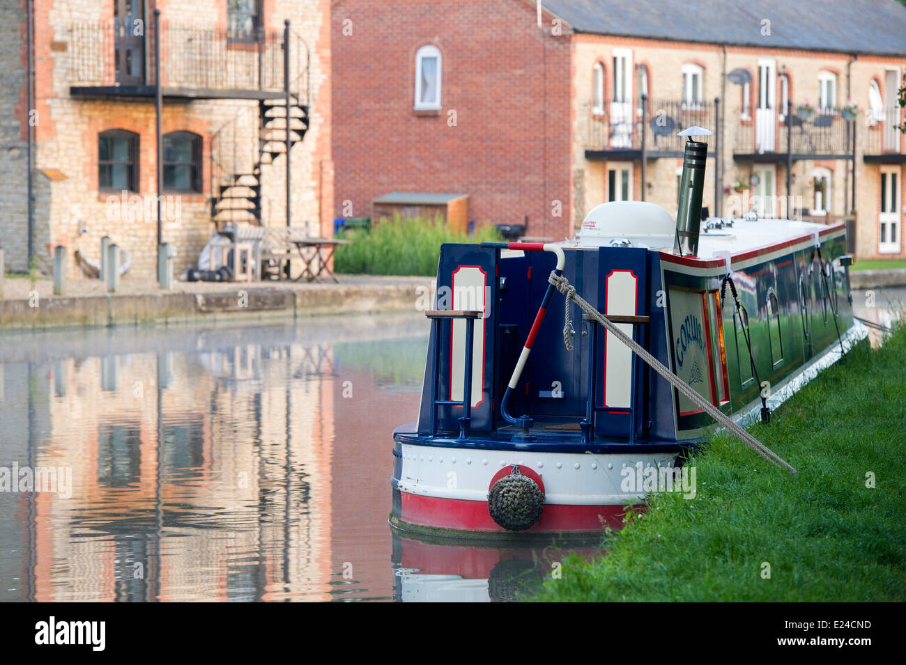 Narrowboat and house reflections on the Grand Union canal. Cosgrove, England - Stock Image