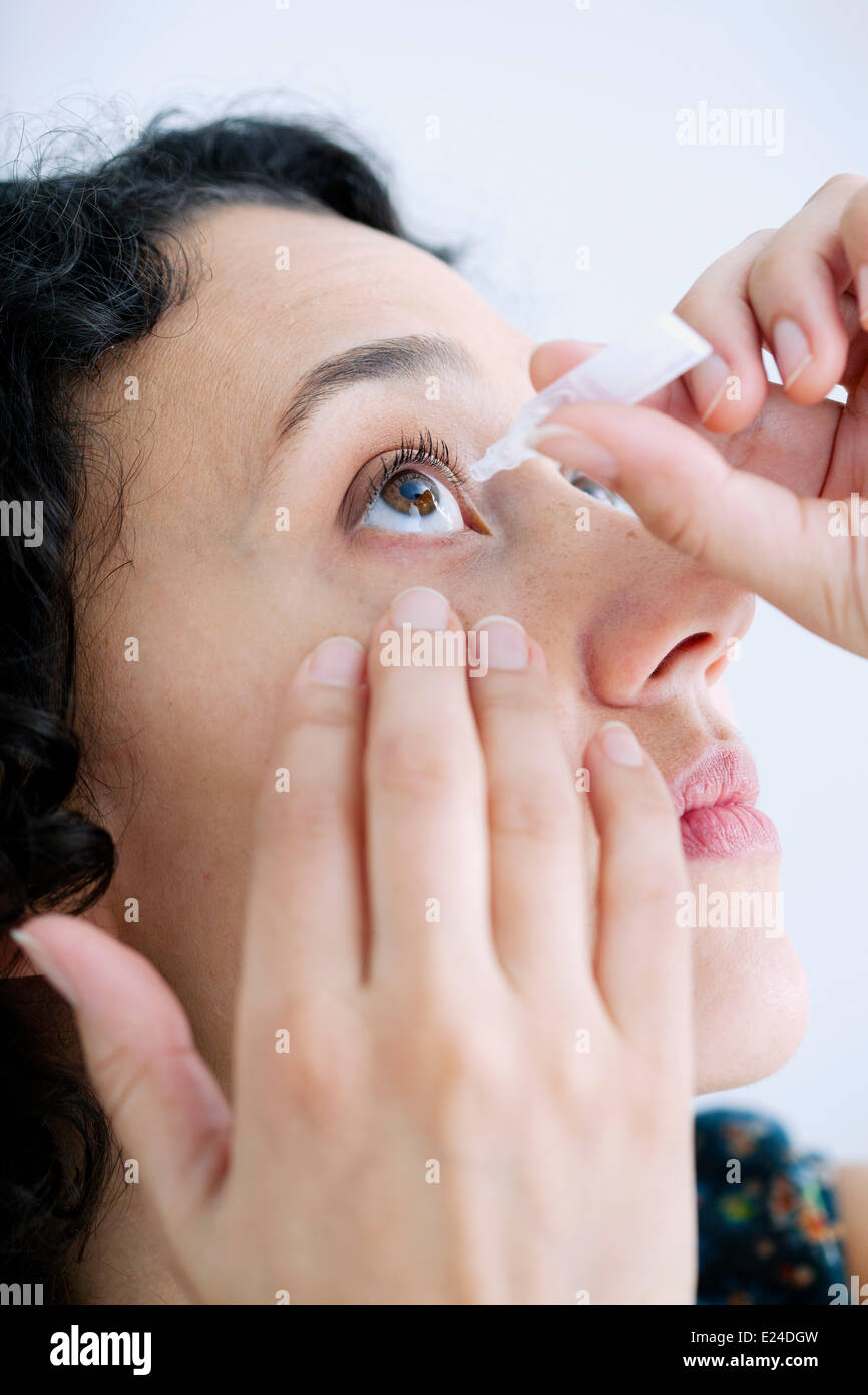 Woman using eye lotion - Stock Image