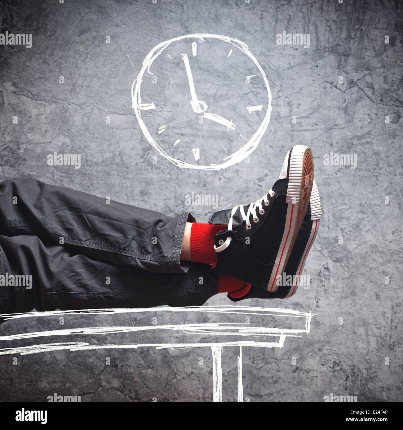 Workday end. Lazy man in sneakers with his legs on the table, few minutes till the end of his working hours. - Stock Image
