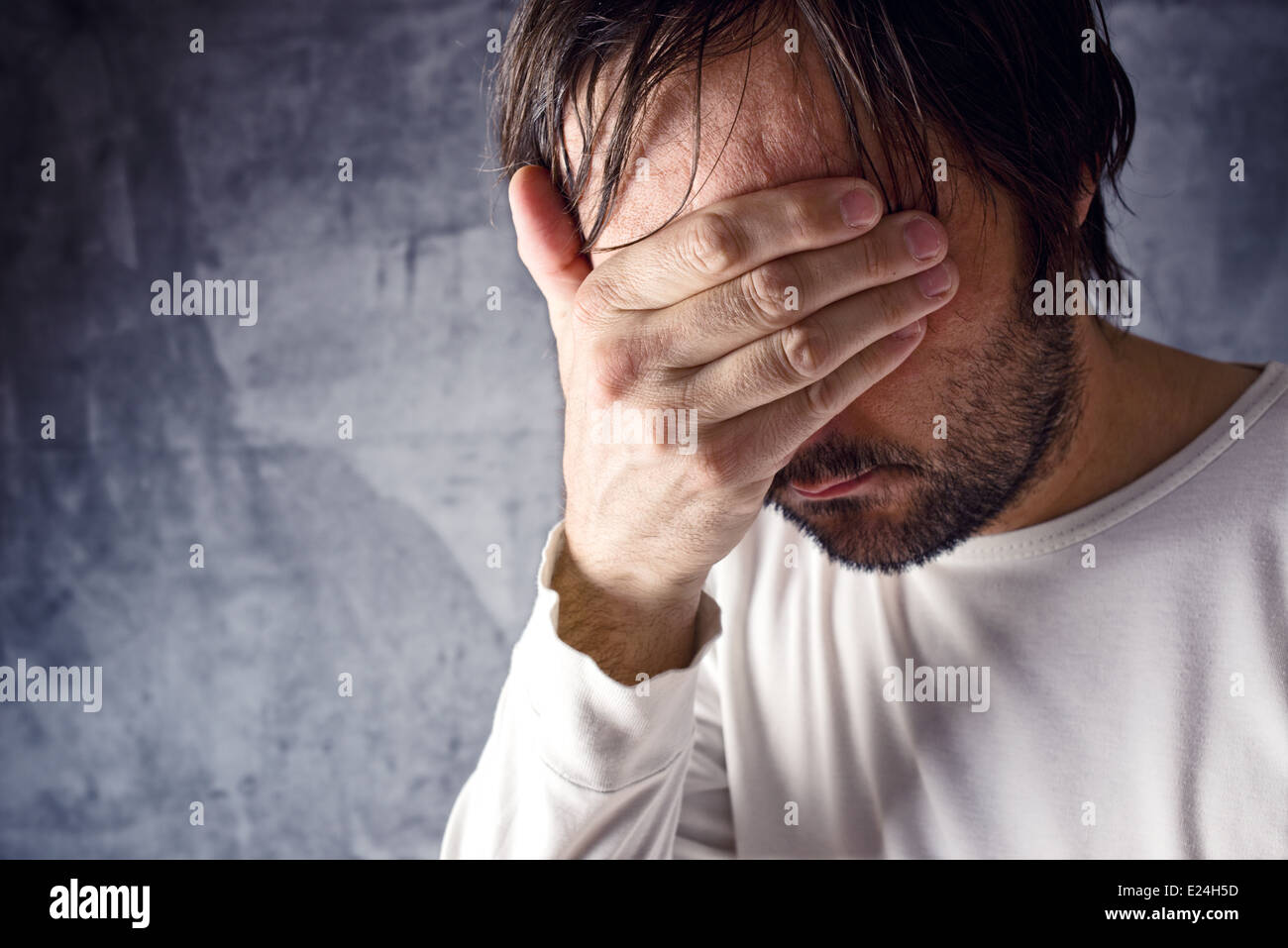 Depressive man crying with hand covering his face, looking upset and showing remorse - Stock Image