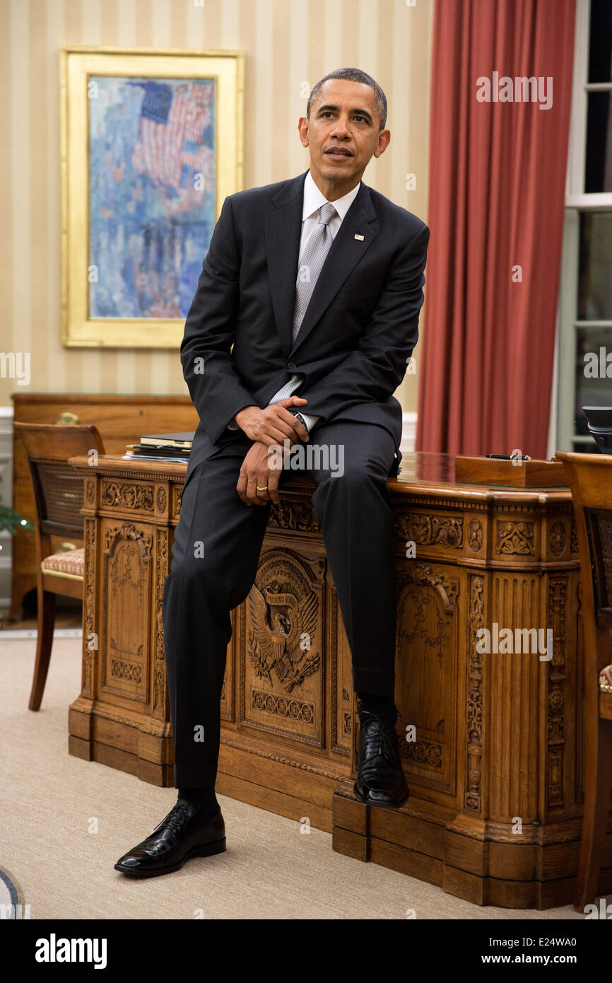 President Barack Obama sits on the edge of the Resolute Desk during a meeting in the Oval Office, Dec. 19, 2012 - Stock Image