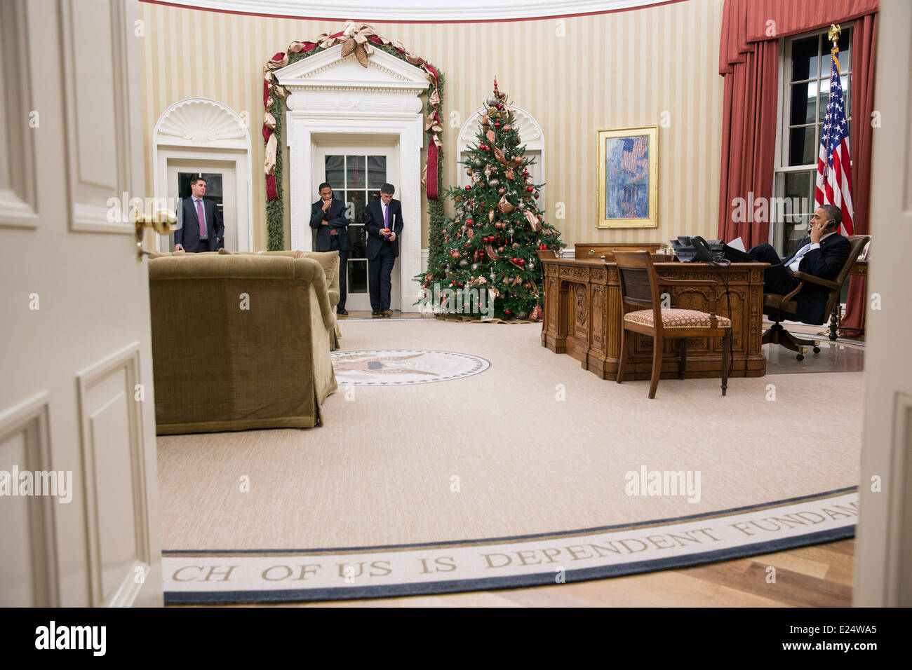 President Barack Obama talks on the phone in the Oval Office, Dec. 11, 2012. Pictured, from left, are: Director Stock Photo